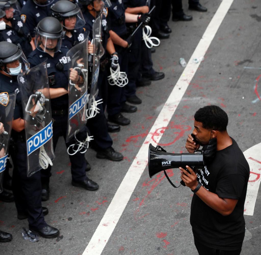 Ein Demonstrant steht vor Beamten des New York Police Department (NYPD) in einem Bereich namens