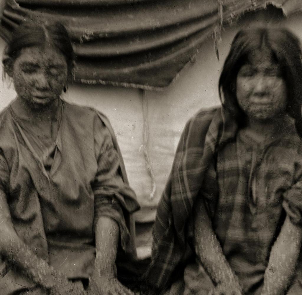 Zwei nicht identifizierte junge Ho-Chunk-Mädchen mit Pocken knien vor ihrem Haus, Black River Falls, Wisconsin, 1900. Einige der Ho-Chunk, die unter Daten litten, wurden während des Ausbruchs von 1901 unter Quarantäne gestellt (Foto von Charles Van Schaick) Bilder abrufen) Getty ImagesGetty Images