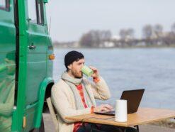 Ein Mann sitzt in einem Fluss an einem Camping-Tisch und benutzt den Vodafone GigaVube