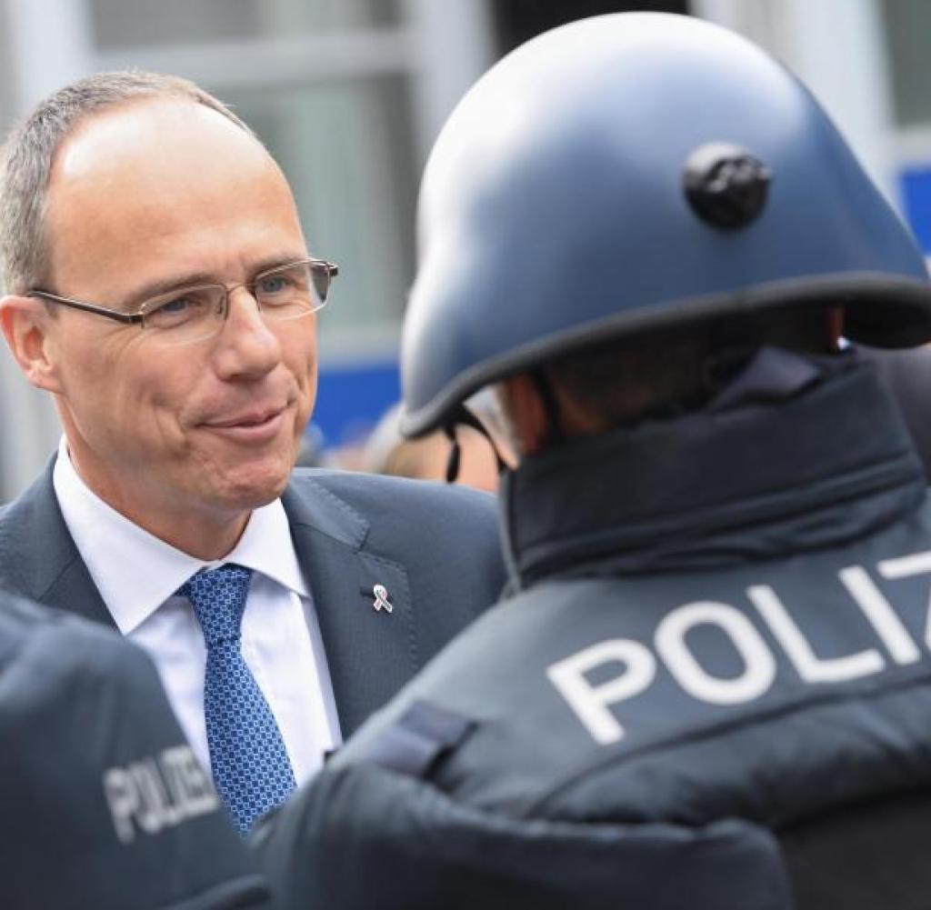 Der hessische Innenminister Peter Beuth (CDU, links) spricht mit einem Polizisten