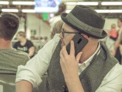 Der Mann telefoniert am Flughafen mit seinem Handy