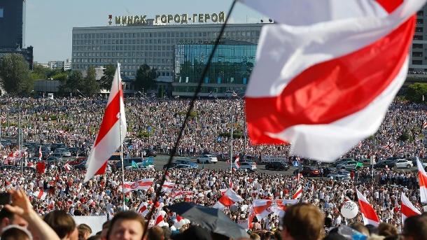 Tausende demonstrieren im Zentrum von Minsk: Demonstranten zeigen die alte Flagge des Landes.  (Quelle: AP / dpa / Sergei Grits)
